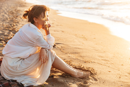 Image of joyful woman 20s sitting on sand and looking at sea while walking along beach