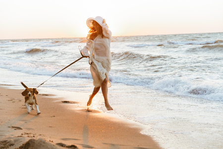 Image of european woman 20s in summer straw hat running by seaside with her dog