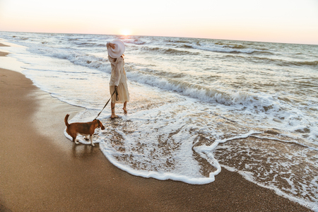 Image of caucasian woman 20s in summer straw hat walking by seaside with her dog