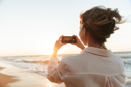 Image of attractive woman 20s taking photo on smartphone while walking by seaside Stock Photo
