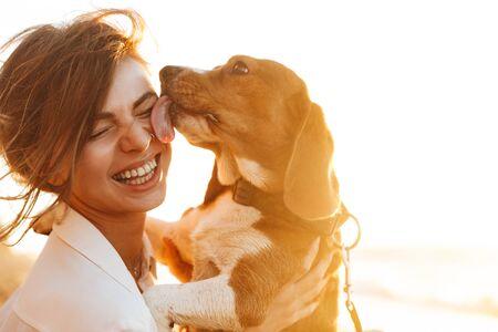 Bild einer glücklichen Frau in den 20ern, die ihren Hund umarmt, während sie auf Sand am Meer sitzt