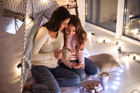 Photo of a happy young woman with her little daughter girl on floor holding cocoa drinking. Christmas concept.