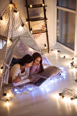 Photo of a happy young woman with her little daughter girl lies on floor using laptop computer. Christmas concept.