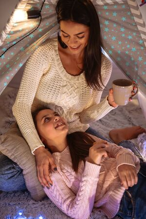 Image of a happy young woman with her little daughter girl hugging on floor holding cocoa drinking. Christmas concept.