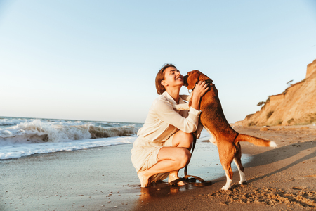 Image of happy woman 20s hugging her dog while walking along the beach Banco de Imagens