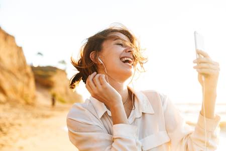 Image of european girl 20s wearing earphones laughing and using mobile phone while walking by seaside