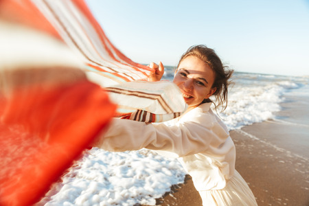 Portrait of cute girl 20s smiling and walking with waving scarf along seashore