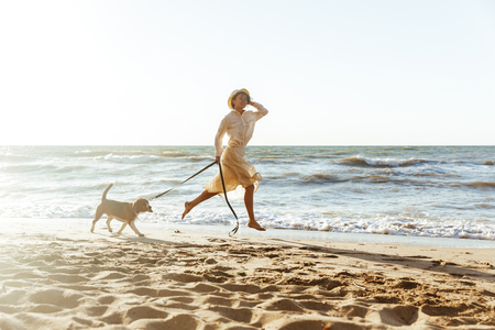 Image of caucasian woman in straw hat running with her brown dog along the coast