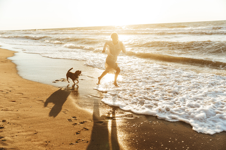 Image of pleased woman 20s running with her dog by seaside in the morning