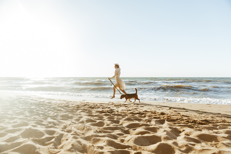Image of happy woman in straw hat running with her brown dog along the coast