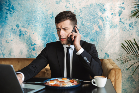 Image of a handsome young businessman sitting in cafe using laptop computer have a breakfast or dinner eat talking by phone. Imagens