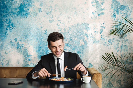 Image of a cheerful handsome young businessman sitting in cafe have a breakfast or dinner eat.