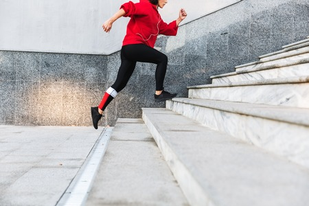 Cropped imge of a young sportswoman running up the stairs outdoors Фото со стока