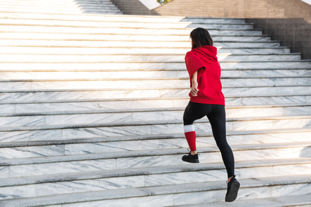 Confident young sportswoman running up the stairs outdoors