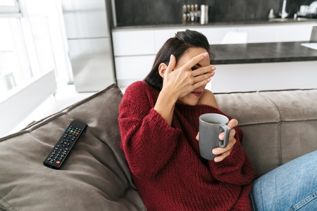 Image of a scared emotional woman indoors in home on sofa watch TV drinking coffee covering eyes.