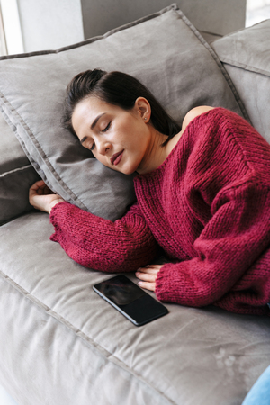 Image of a woman indoors in home on sofa sleeping have a rest lies. Stok Fotoğraf - 118208805