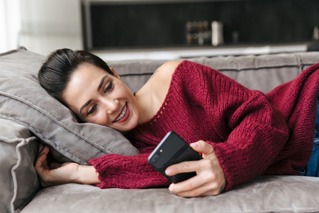 Image of a beautiful woman indoors in home on sofa using mobile phone. Banco de Imagens