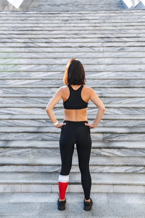 Back view of a confident young sports woman resting after exercising outdoors