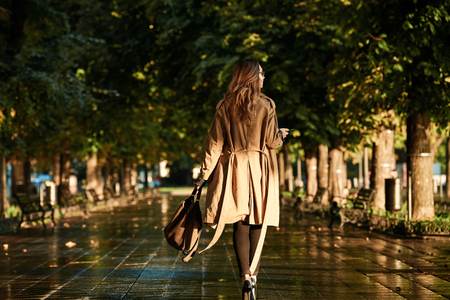 Portrait of adorable woman 20s wearing coat and eyeglasses using mobile phone while walking through empty boulevard