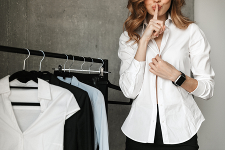Cropped photo of beautiful young business woman dressed in formal clothes shirt indoors showing silence gesture. Фото со стока