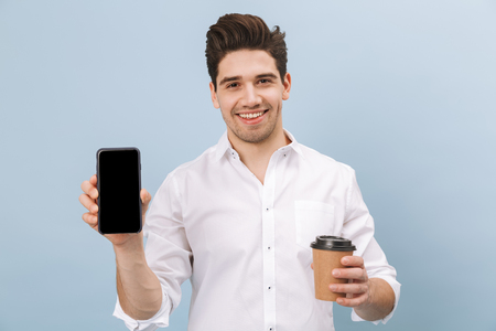 Portrait of a cheerful handsome young man standing isolated over blue background, holding takeaway coffee cup, showing blank screen mobile phone Stockfoto