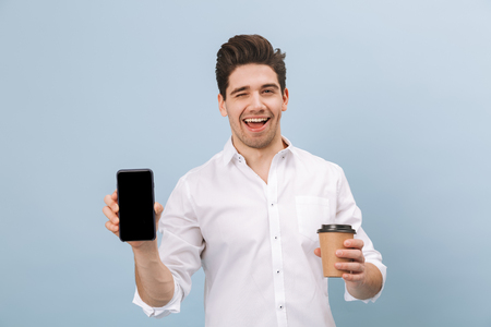 Portrait of a cheerful handsome young man standing isolated over blue background, holding takeaway coffee cup, showing blank screen mobile phone 写真素材