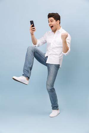 Volledig portret van een vrolijke, knappe jonge man die geïsoleerd staat over een blauwe achtergrond, mobiele telefoon vasthoudt en viert