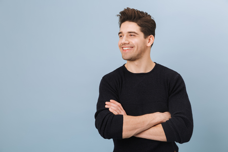 Portrait of a cheerful handsome young man standing isolated over blue background, looking away