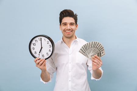 Portrait of a cheerful handsome young man standing isolated over blue background, showing money banknotes, showing alarm clock Banque d'images - 118210635