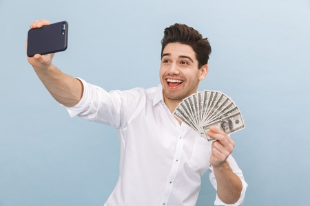 Portrait of a cheerful handsome young man standing isolated over blue background, showing money banknotes, taking a selfie