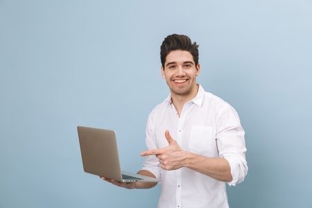 Portrait of a cheerful handsome young man standing isolated over blue background, working on laptop computer Stock Photo