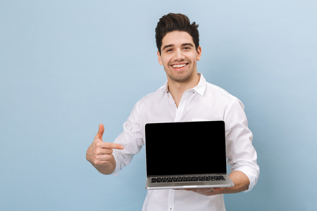 Portrait of a cheerful handsome young man standing isolated over blue background, working on laptop computer, showing blank screen laptop Stock Photo