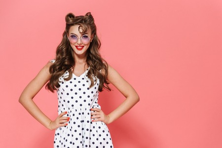 Portrait of a beautiful young pin-up girl wearing dress and sunglasses standing isolated over pink background, posing 版權商用圖片