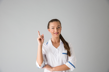 Photo of a beautiful young woman cosmetologist doctor isolated over grey wall background pointing. Stock Photo