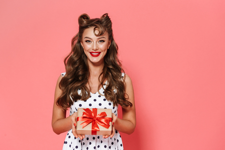Portrait of a beautiful young pin-up girl wearing dress standing isolated over pink background, showing gift box Stock Photo