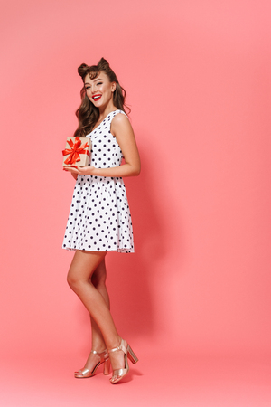 Full length portrait of a beautiful young pin-up girl wearing dress standing isolated over pink background, showing gift box