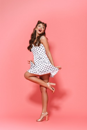Full length portrait of a beautiful young pin-up girl wearing dress standing isolated over pink background, posing