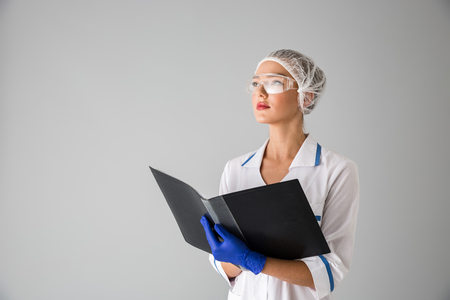 Image of a beautiful young woman cosmetologist doctor isolated over grey wall background holding folder.