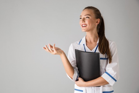 Photo of a beautiful happy young woman cosmetologist doctor isolated over grey wall background holding folder.