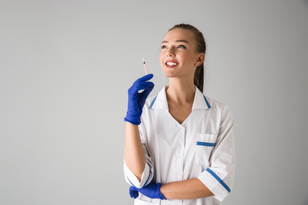 Photo of a beautiful young woman cosmetologist doctor isolated over grey wall background holding injection syringe. Stock Photo - 118513125