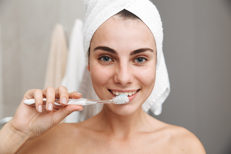 Close up of a beautiful young woman with towel on her head standing at the bathroom, brushing teeth Фото со стока