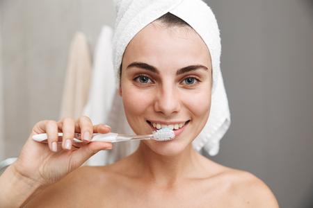 Zbliżenie na piękną młodą kobietę z ręcznikiem na głowie, stojącą w łazience, myjącą zęby