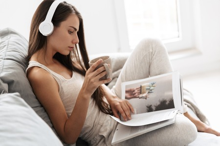 Image of beautiful young woman sitting on sofa indoors at home listening music with headphones drinking tea reading magazine.