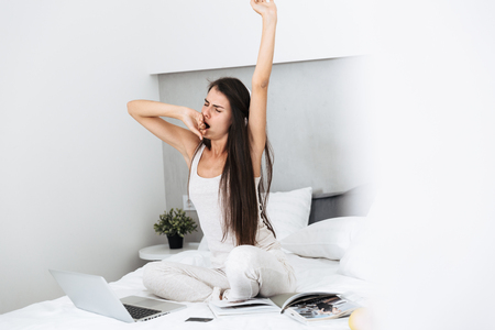 Beautiful young woman relaxing on bed at home, listening to music with headphones