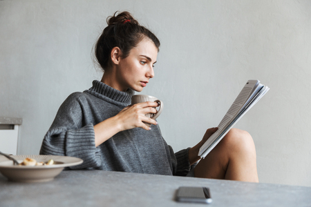 Beautiful young woman having healthy breakfast while sitting on a kitchen, reading magazine Stockfoto