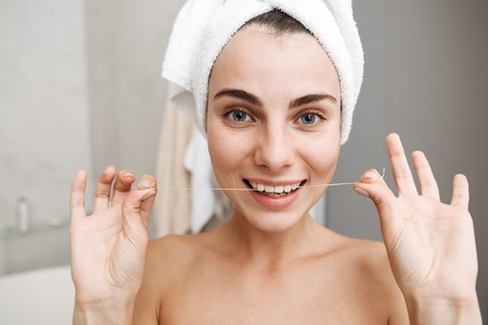Close up of a beautiful young woman with towel on her head standing at the bathroom, using teeth floss Stock Photo