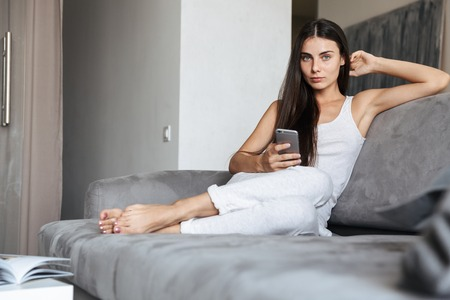 Image of pretty beautiful young woman sitting on sofa indoors at home using mobile phone chatting.