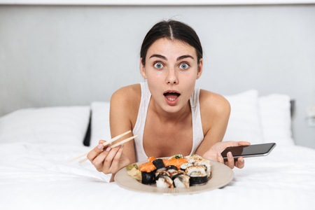 Beautiful young woman relaxing on bed at home, eating sushi from a plate, holding mobile phone