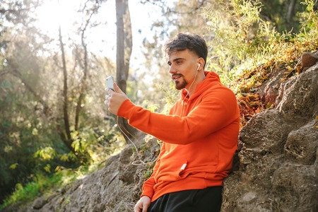 Picture of handsome young sports fitness man runner outdoors in park listening music with earphones using mobile phone take a selfie talking. Stock Photo