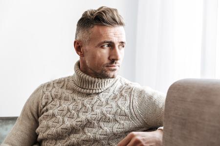 Image of a handsome man work indoors on sofa looking aside. Foto de archivo - 118736377
